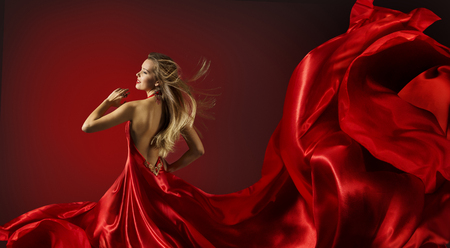 Foto de Woman in Red Dress Dancing, Fashion Model with Flying Cloth Fabric - Imagen libre de derechos