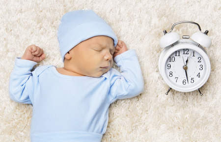 Foto de Sleeping Newborn Baby and Clock, New Born Sleep in Bed - Imagen libre de derechos