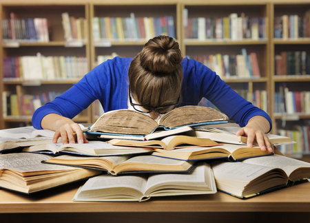 Foto de Student Studying Hard Exam and Sleeping on Books, Tired Girl Read Difficult Book in Library - Imagen libre de derechos