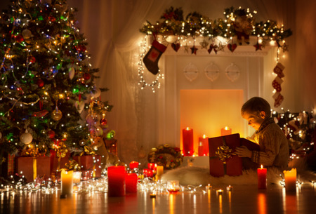 Foto de Child Opening Christmas Present, Kid Looking to Light Gift Box, Night Room Xmas Tree and Fireplace - Imagen libre de derechos