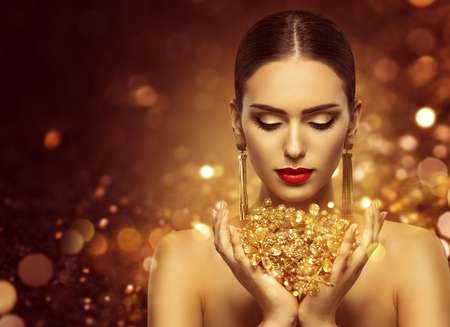 Foto de Fashion Model Holding Gold Jewelry in Hands, Woman Golden Beauty, Beautiful Girl Makeup and Luxury Jewellery - Imagen libre de derechos