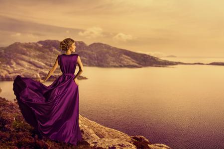 Foto de Woman in Elegant Dress on Mountain Coast, Fashion Model in Flowing Gown Cloth, Looking to Landscape View, Outdoor - Imagen libre de derechos