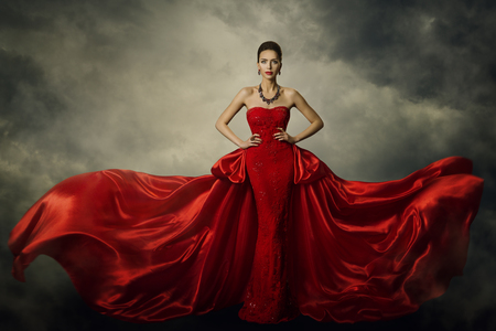 Photo pour Fashion Model Art Dress, Elegant Woman Standing in Red Retro Gown, Silk Fabric Fluttering over Storm Sky Background - image libre de droit