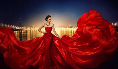 Foto de Fashion Model in Fluttering Dress in Night City Street Lights, Elegant Woman in Red Long Gown, full length beauty portrait - Imagen libre de derechos