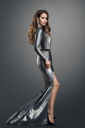 Photo pour Fashion Model in luxury Silver long Dress. Elegant Woman with Curly Long Hair Hairstyle in Evening Gown with Slit showing Leg over dark Gray Studio Background - image libre de droit