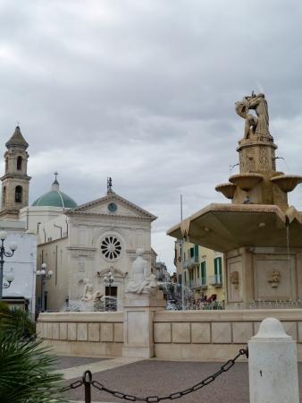 The Maddalena church and the monumental fountain on the twentieth September square in Mola di Bari in Apulia in Italy