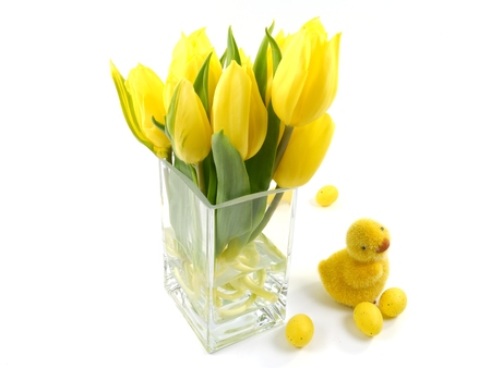 Yellow spring tulips in a vase of glass with an Easter decoration over white