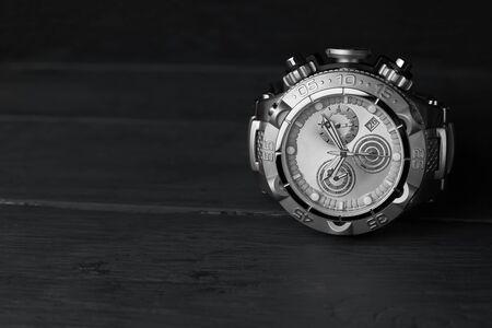 Foto de Stainless steel wristwatch on a dark wooden background. - Imagen libre de derechos