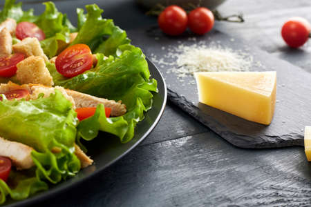Photo for Delicious Caesar salad with cherry tomatoes and croutons and piece and grated parmesan cheese on black serving board. - Royalty Free Image
