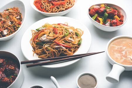 Photo for Assorted Indo chinese food in group includes non vegetarian or chicken Schezwan/Szechuan hakka noodles, fried rice, manchurian, egg american chop suey, soup with spoon and chop sticks, selective focus - Royalty Free Image