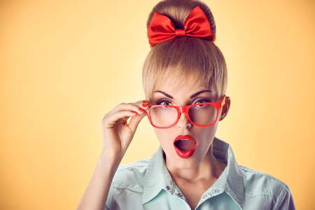 Beauty fashion portrait business woman, stylish red glasses surprised, open mouth, shocked. Attractive blonde girl, confidence, Pinup hairstyle bow makeup.Unusual playful, emotions.Vintage, on yellow
