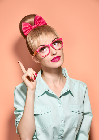 Beauty fashion hipster woman in stylish glasses thinking, idea. Attractive pretty funny blonde girl smiling. Confidence, success, Pinup hairstyle bow makeup. Unusual playful, expression.Vintage, pink