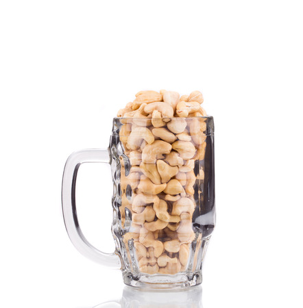 Cashew in a glass. Isolated on a white background.