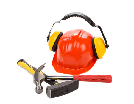 Ear muffs on hard hat and hammer. Isolated on a white background.