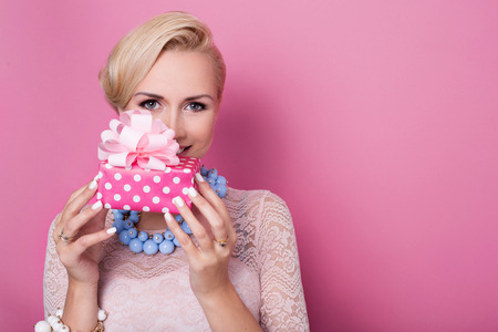 Happy birthday. Sweet blonde woman holding small gift box with ribbon. Soft colors. Studio portrait over pink background