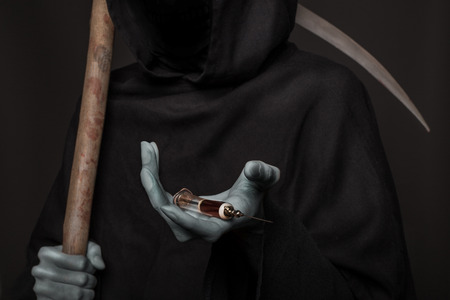 The concept: drugs kill. Angel of death holding syringe with heroin. Studio shot over black background