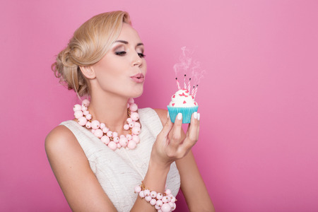 Beautiful women with cream dress holding small cake with colorful candle. Birthday, holiday. Studio portrait over pink background