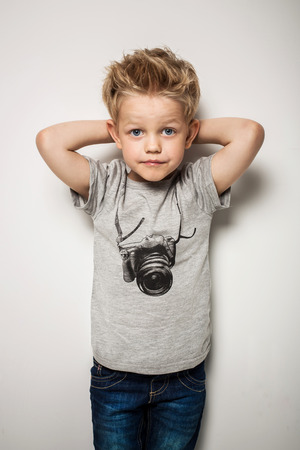 Little pretty boy posing at studio as a fashion model. Studio portrait over white background