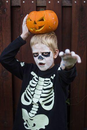 Foto de Happy young blond hair boy with skeleton costume holding jack o lantern. Halloween. Trick or treat. Outdoors portrait - Imagen libre de derechos