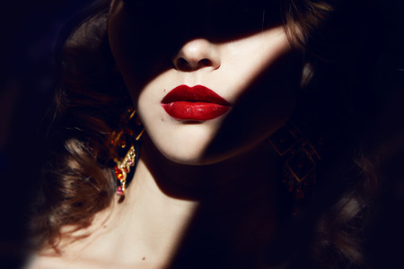Photo pour Closeup of the face belong to beautiful young sexy blonde girl with curly hair pure snow white skin and bright makeup red lips, red lipstick, long earrings in dark shadows of palm leaves - image libre de droit