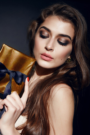 Beautiful young sexy brunette woman with bright evening make-up perfect smooth skin cosmetics cream face care, jewelry, beauty salon, magazine, close-up portrait with box present
