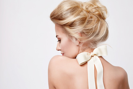 Foto de Tender fashion portrait of beautiful gentle young blond woman with silk bow on the neck cosmetics for body face hair pure natural beauty, organic and diet harmony, makeup - Imagen libre de derechos
