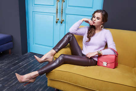 Beautiful sexy brunette woman sitting on a couch, wearing a stylish fashionable tight pants eco leather cashmere sweater, clothing catalog, red bag, room interior, door.の写真素材