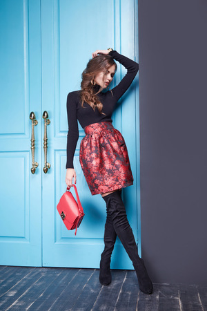 Foto de Stylish fashionable outfit slim beautiful girl figure diet, catalog collection of clothing, attractive, sexy woman wearing red skirt classic fitting black sweater, leather small handbag room blue door. - Imagen libre de derechos