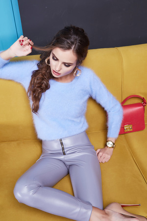 Beautiful woman lady wear cashmere sweater and leather trousers seat on the yellow sofa blue door furniture interior clothes fashion style sexy collection brand bag store sale