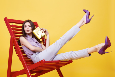 Photo pour Glamour sexy girl clothes violence color silk blouse with lace beige cotton pants sit on chair  relax break hold trend bag stylish shoes beautiful face long brunette hair fashion collection model pose - image libre de droit