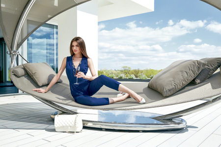 Photo for Brunette sexy woman glamour fashion luxury life style lady sit on stylish hammock modern interior building house party time drink champagne accessory lather bag summer blue sky nature resort success. - Royalty Free Image