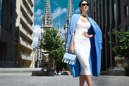 Foto de Beautiful sexy fashion stylish female model long dark hair wearing natural make-up in chic slinky dress Knit long coat jacket accessory sunglasses bag shoes jewelry vintage city church modern building - Imagen libre de derechos