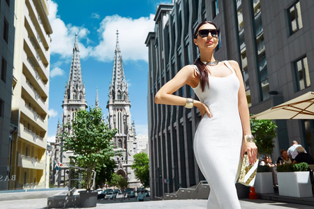 Foto de Sexy glamour woman in white fashion style dress with handbag accessory and golden jewelry businesswoman walk buildings and trees street brunette wear shoes makeup lady date party meeting pose - Imagen libre de derechos