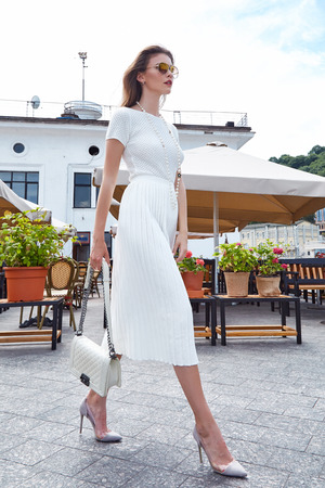 Foto per Brunette sexy woman fashion style street look elegant walk cafe restaurant date meeting businesswoman success wear white dress accessory bag sunglasses high-heels shoes clothes summer collection. - Immagine Royalty Free