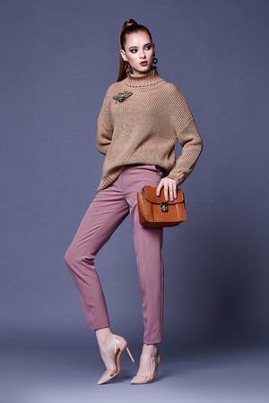 Photo pour Sexy beautiful woman perfect body shape pretty face make up wear beige wool cashmere sweater and pink pants high heels shoes accessory bag casual clothes for party walk brunette hair fashion style. - image libre de droit