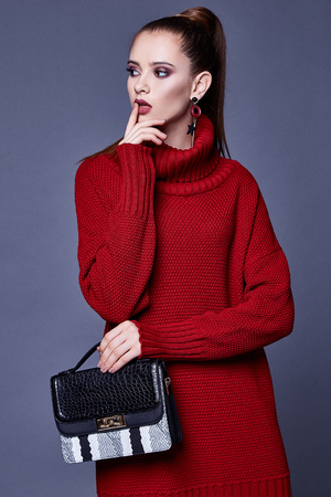 Foto de Fashion style woman perfect body shape brunette hair wear red knitted dress wool organic clothes sexy lady casual glamour accessory bag high heels shoes jewelry beautiful face makeup designer. - Imagen libre de derechos
