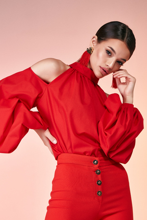 Pretty beautiful sexy elegance woman fashion model glamor pose wear red color trousers silk blouse clothes for party summer collection makeup hair style brunette success accessory bag jewelry studio.