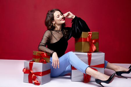 Foto per Beautiful young pretty woman with a bright evening make-up of shiny red lipstick on the lips brunette curly hair festive mood winter Christmas New Year St. Valentine's Day and birthday gift surprise. - Immagine Royalty Free