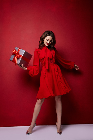Photo pour Beautiful young sexy woman thin slim figure evening makeup fashionable stylish dress clothing collection, brunette, gifts boxes red silk bows holiday party birthday New Year Christmas Valentine's Day. - image libre de droit