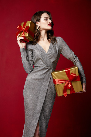 Foto de Beautiful sexy young brunette woman hair bright evening make-up red lips long fluffy eyelashes hold gift box holiday New Year  joy fun happy merry Christmas Eve party celebration St. Valentine's Day. - Imagen libre de derechos