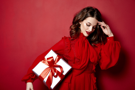 Foto per Beautiful young sexy woman thin slim figure evening makeup fashionable stylish dress clothing collection, brunette, gifts boxes red silk bows holiday party birthday New Year Christmas Valentine's Day. - Immagine Royalty Free