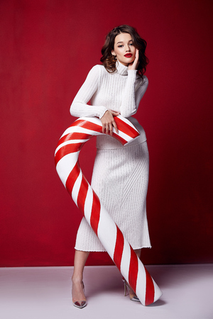 Foto de Sexy pretty lady fashion model beautiful woman wear style skinny knitted white color dress celebration happy holidays merry Christmas Eve new year party hold candy cane caramel brunette makeup. - Imagen libre de derechos