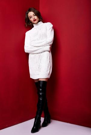 Foto de Beautiful sexy pretty woman red lipstick jewelry earrings brunette hair cosmetic makeup fashion wear clothes style beauty salon happy party style Valentine's red background accessory brunette. - Imagen libre de derechos