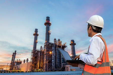 Foto de Engineering is use notebook check and standing in front of oil refinery building structure in heavy petrochemical industry - Imagen libre de derechos
