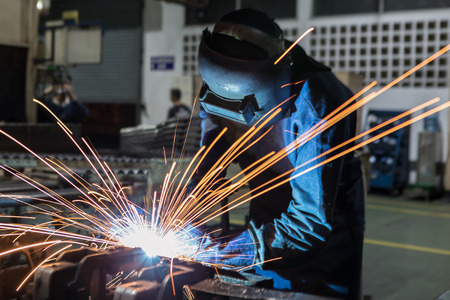 Photo for Industrial Worker at the factory is welding automotive part - Royalty Free Image