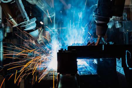 Photo pour Team industrial robots are welding in factory - image libre de droit