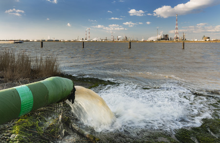 Photo pour A wastewater pipe and a large oil refinery in the harbor of Antwerp, Belgium with blue sky and warm evening light. - image libre de droit