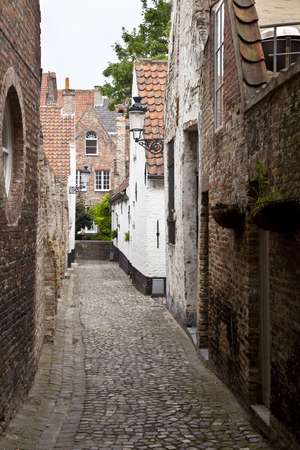One of the many narrow alleys in the city of Bruges on a cloudy day.