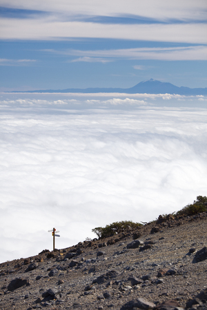 View from the Pico de la Nieve in La Palma, Spain to Tenerife like floating on clouds, a way sign in the foreground.