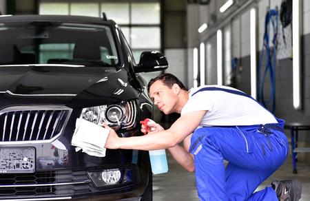Photo pour professional car wash - worker in a car dealership polishes the car paint - image libre de droit